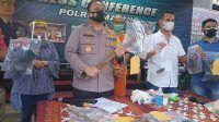 Kapolres Malang memegang cangkul sebagai barang bukti kasus pembunuhan