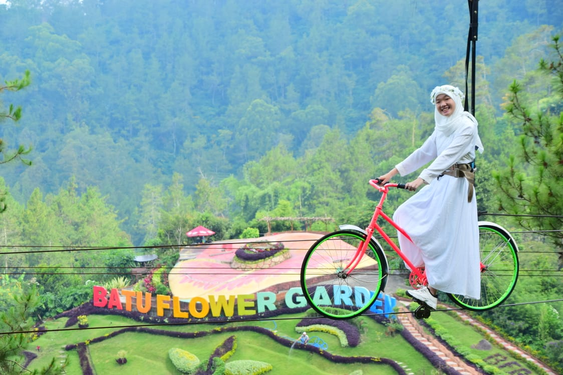 Foto: Wisatawan menikmati salah satu wahana yaitu gowes air di Batu Flower Garden (Batu Flower Garden)